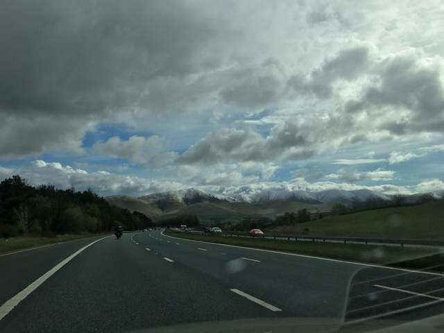Three lane motorway with snowy mountain range in the distance